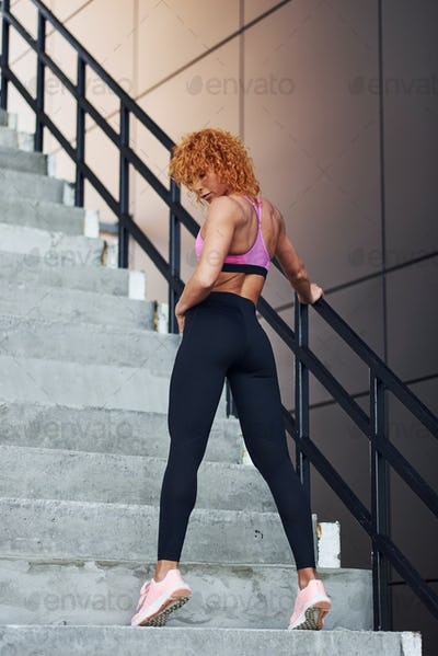 Young european redhead woman in sportive clothes showing her body and posing outdoors