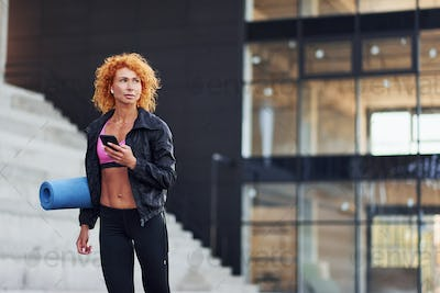 Young european redhead woman in sportive clothes with phone and mat in hands outdoors