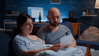 Desperate young couple reading eviction notice in paperwork letter