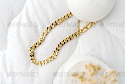 Golden modern bijouterie chain on white background.