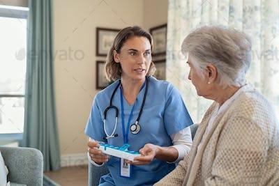 Nurse explaining medicine dosage to senior woman at nursing home