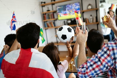 Diverse friends sports fans watching football match on TV at home. Celebrating shouting excited