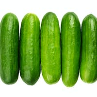 Snack cucumbers in a row, young cucumber fruits in wooden bowl