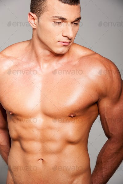 Strength and masculinity. Handsome young muscular man posing while standing against grey background