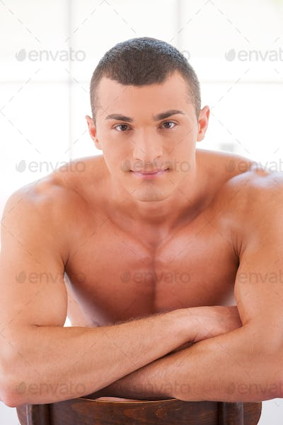 Strong muscular man. Handsome young muscular man sitting on the chair and looking at camera