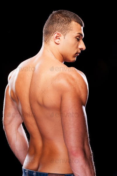 Muscular handsome. Rear view of young muscular man standing against black background