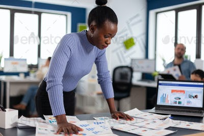 Black businesswoman checking work of multiethnic colleagues