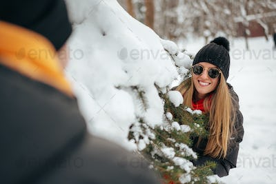 Young loving couple play hide and seek in a snowy winter park