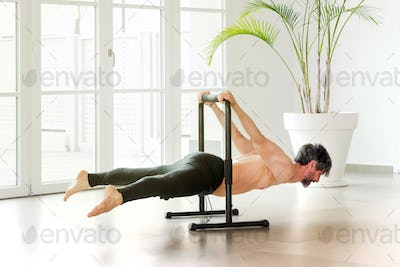 Man performing a back lever calisthenics pose on a bar