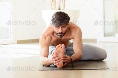 Man performing a Janu sirsana yoga pose
