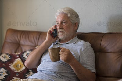 Serious senior aged man doing phone call sitting at home with smart phone - sad emotion