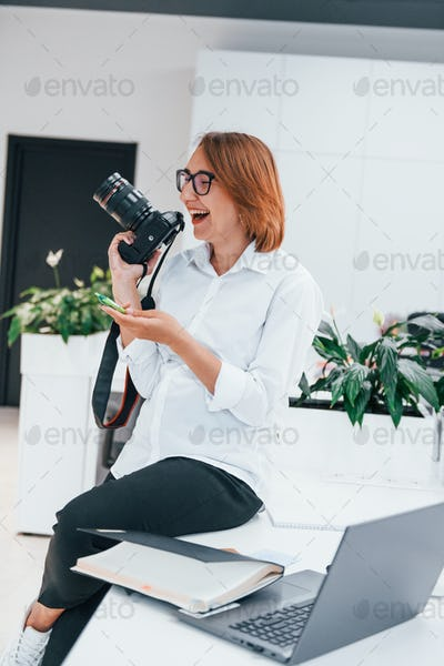 Woman in formal clothes and with camera sitting in the office