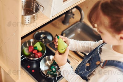Little girl in casual clothes have fun by playing with toys on the kitchen