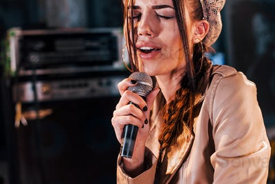 Young beautiful female performer rehearsing in a recording studio