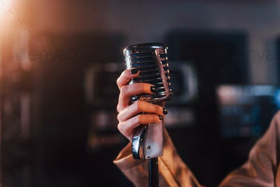 Close up view of microphone. Young beautiful female performer rehearsing in a recording studio