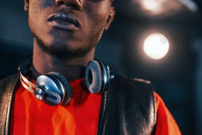 Young african american performer standing in a recording studio and holding headphones