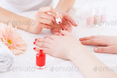 Manicurist in action. Close-up of manicurist doing red manicure to female customer
