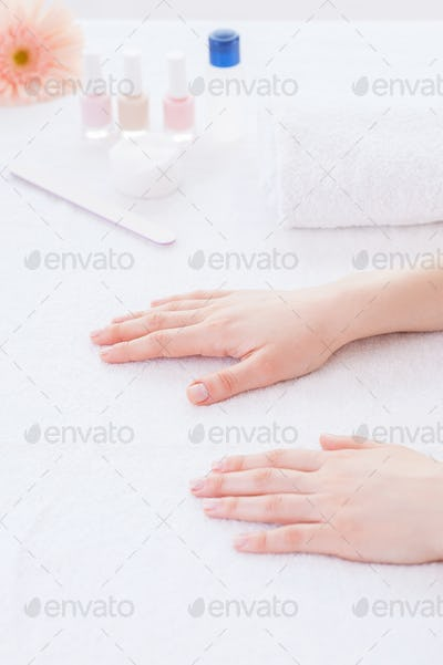 Preparing hands for manicure. Close-up of female hands on the table for manicure
