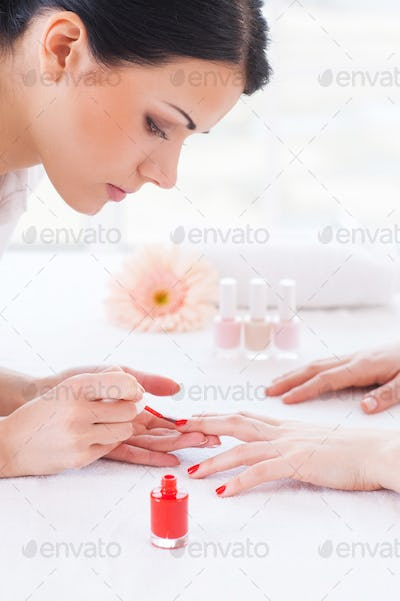 Making red manicure. Close-up of beautician doing red  manicure to female customer