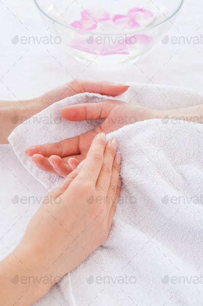 Beauty treatment. Close-up of beautician drying customers hand with towel