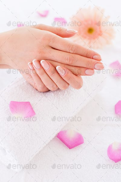 So clean and smooth. Close-up of beautiful female hands on the towel with rose petals laying around