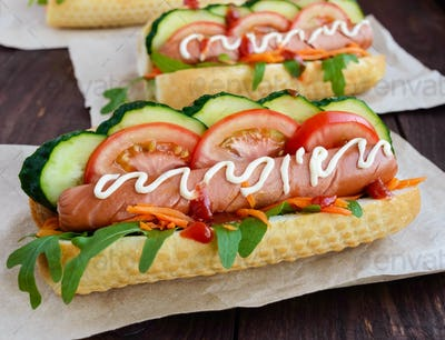 Home made hot dogs with vegetables, juicy sausage and arugula on the wooden background. Close-up.
