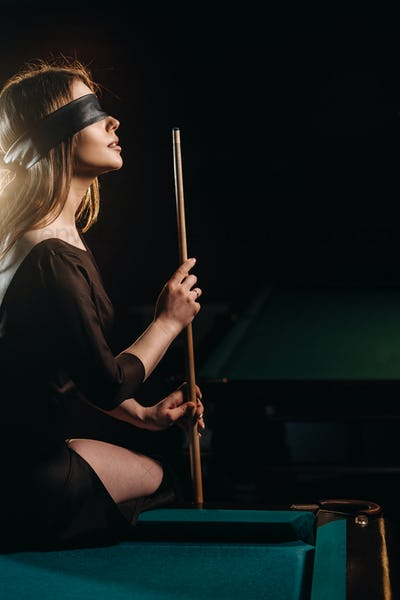 A girl with a blindfold and a cue in her hands is sitting on a table in a billiard club
