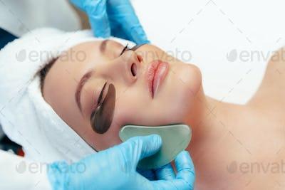 Beautiful woman having guasha scraper face massage done by cosmetologist