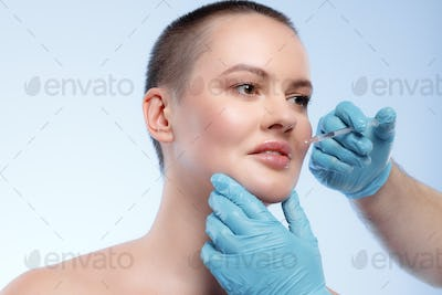 Beautiful woman with short hair gets a beauty injection in her face