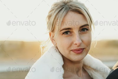 Portrait of a smiling woman standing outdoors in furcoat