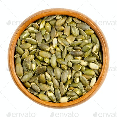 Hulled, roasted, salted pumpkin seeds, in a wooden bowl