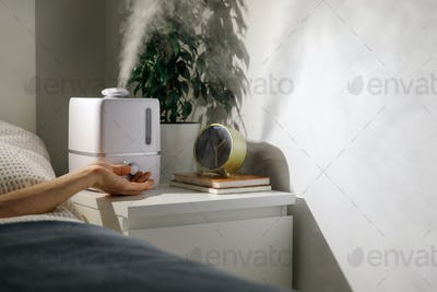 Hand turn on humidifier on bedside table at home