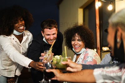 Happy multiracial people cheering with cocktails at terrace party wearing safety masks