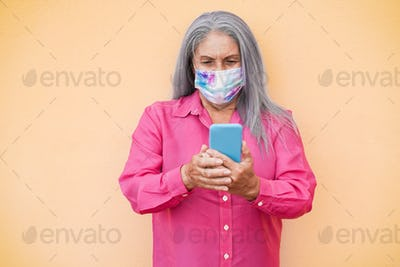 Happy senior woman wearing protective face mask using mobile phone outdoor - Focus on face
