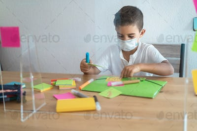 Boy child with mask learning art lesson at preschool during coronavirus outbreak - Focus on kid face
