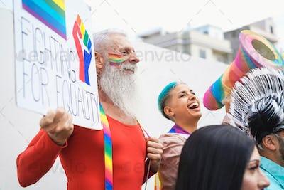 Happy senior gay man holding banner at pride lgbt festival - Focus on left face