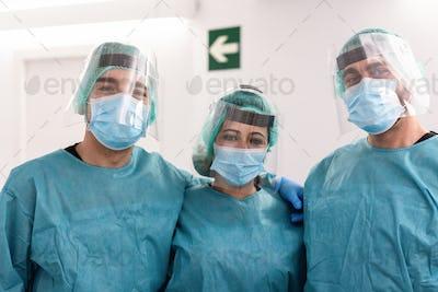 Portrait of medical doctors looking at camera inside hospital corridor