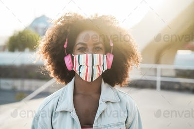 Black girl listening music with headphones while wearing face mask outdoor