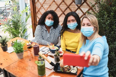 Happy multiracial friends taking selfie outdoors in restaurant - Focus on middle girl