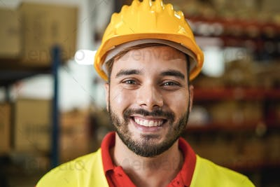 Portrait of man worker smiling on camera inside warehouse - Focus on mouth