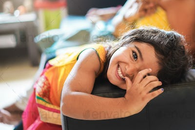 Happy indian child having fun sitting on sofa with parents at home - Focus on girl