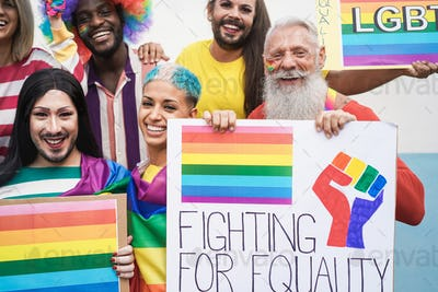 Multiracial gay people having fun at pride parade with LGBT flags and banners outdoors