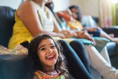 Happy indian girl child wearing sari dress sitting on sofa with parents at home - Focus on girl face