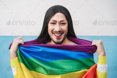 Happy drag queen wearing lgbt rainbow flag - Focus on face