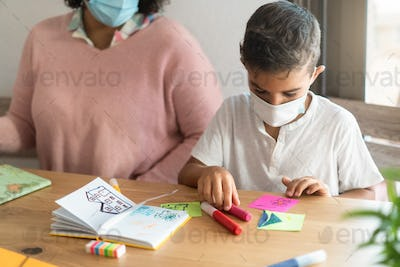 Child boy wearing safety mask in classroom while wearing safety mask - Focus on kid face