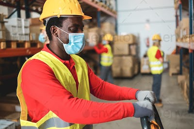 Afro american worker inside warehouse pulling a pallet truck while wearing safety mask
