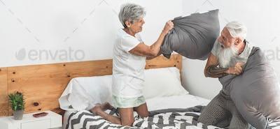 Senior couple doing pillow battle inside home bedroom