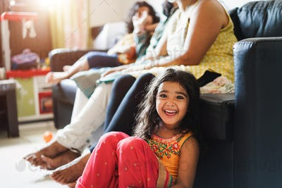 Indian family having fun at home sitting on sofa - Focus on child face