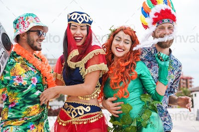 Happy dressed people celebrating at carnival party dancing together - Main focus on right woman face