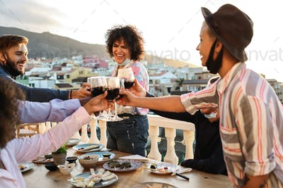 Happy young multiracial friends cheering with wine and eating outdoors